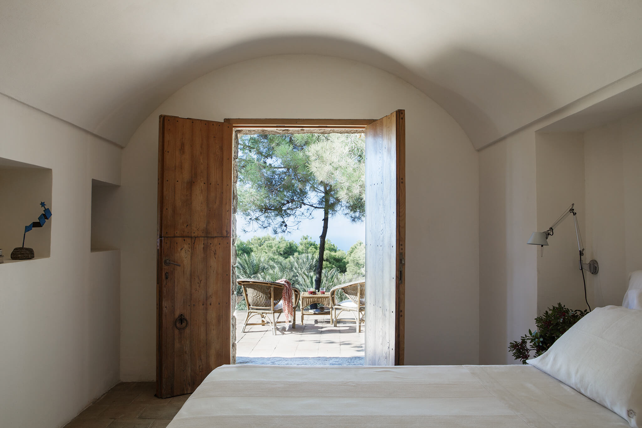 Beautiful natural looking bedroom with door open and vista out to pine trees