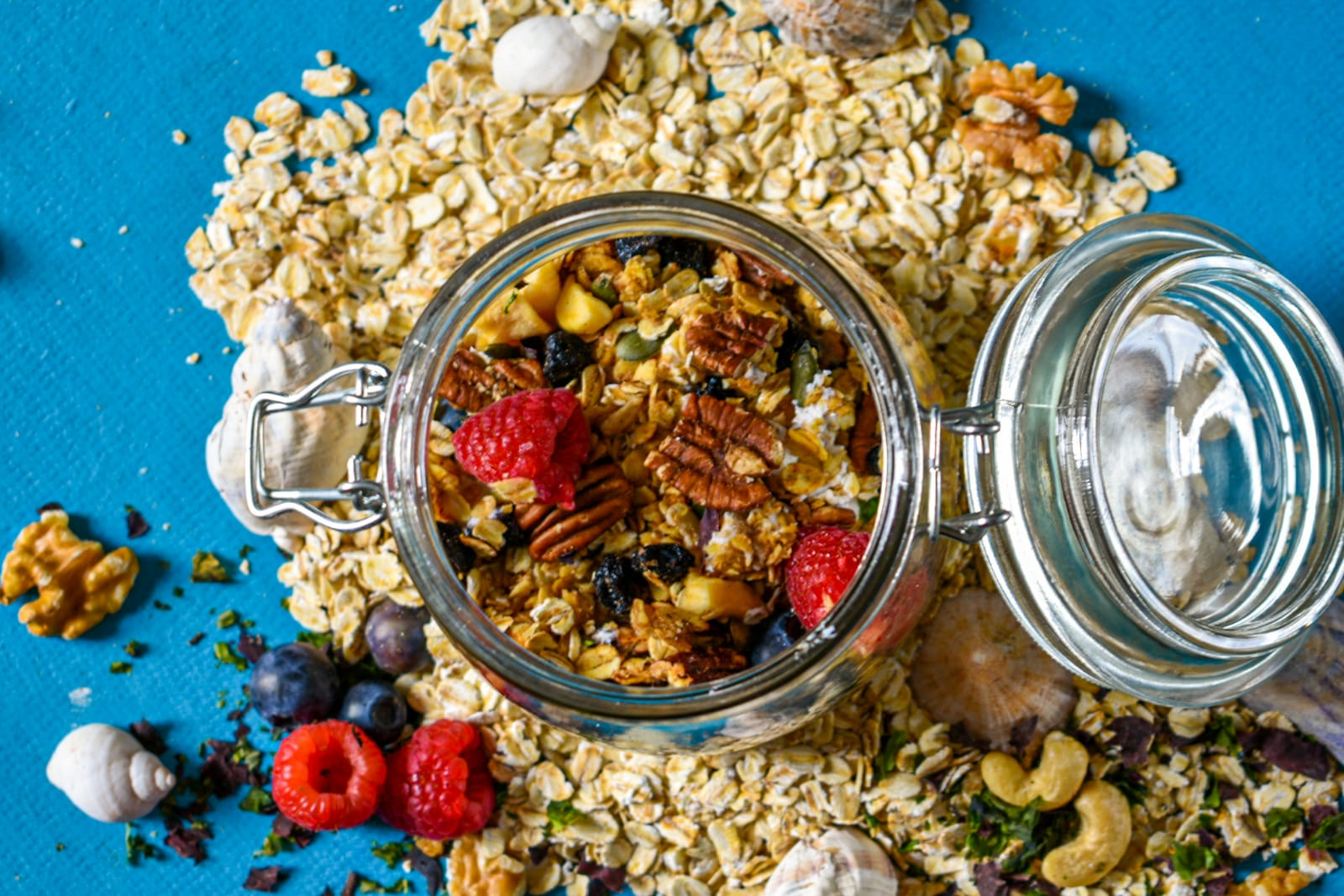 Close-up shot of granola in glass jar with granola outside on the bench around it
